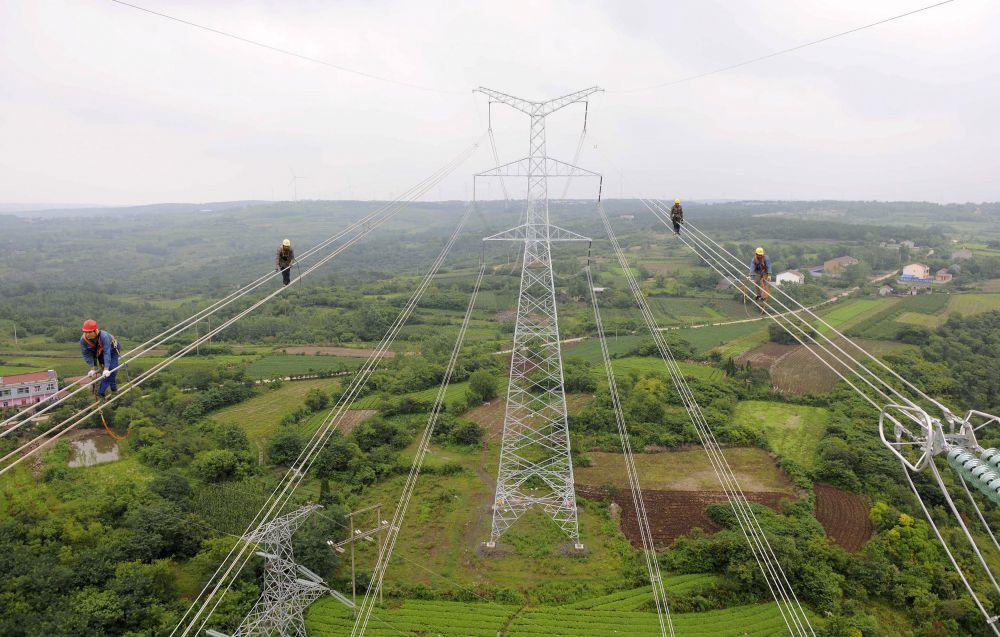 9 июля, Китай. Работники ходят по проводам для проверки построенных линий электропередач.