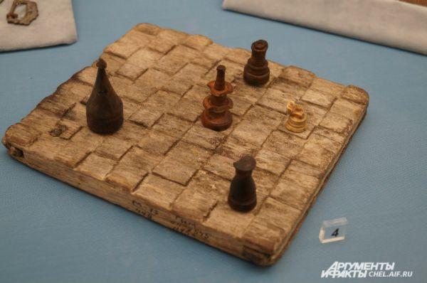 Шахматная доска с фигурами, вырезанная из дерева. Подобные имелись у жителей Мангазеи ещё в XVI веке.