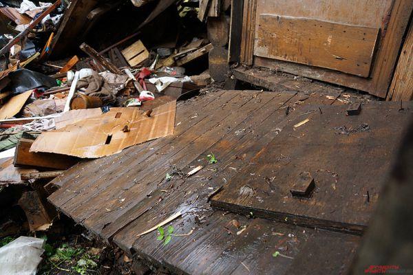 Входную дверь в дом завалило грудой мусора.