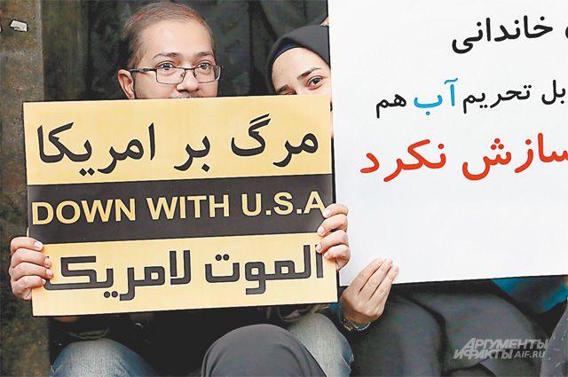 Иран прекращает ядерную программу, однако внешняя и внутренняя политика страны остаётся прежней. Надпись на плакатах - «Долой США!».