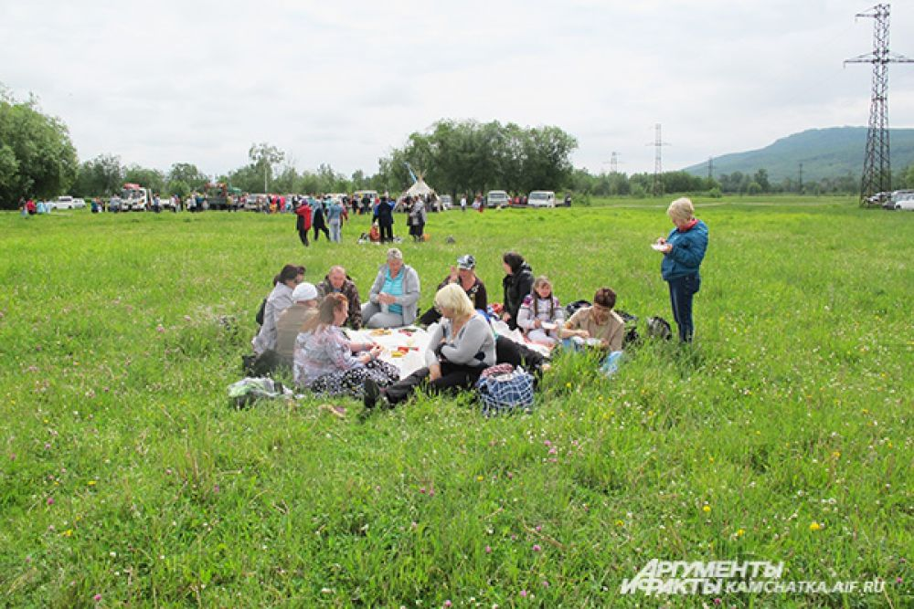 Гости праздника отдыхают на полянах, пробуя национальные славянские угощения.