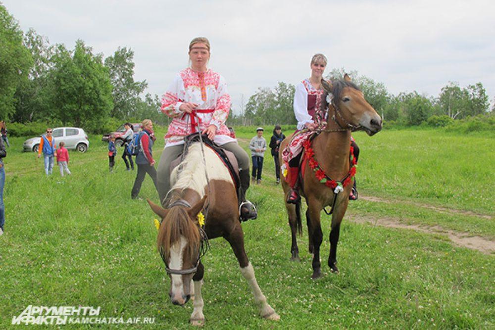 В расшитых платьях и рубашках, с лентами в косах восседали девушки на лошадях.
