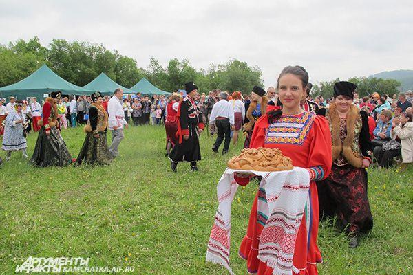 Славянская красавица угощала гостей праздника вкуснейшим белым хлебом.