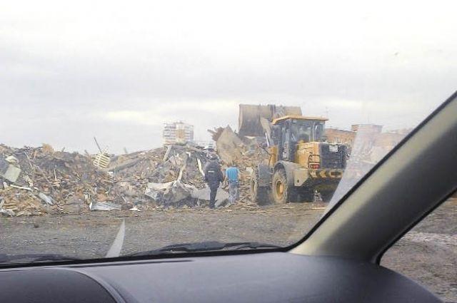 Полицейский координирует выгрузку мусора.