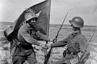 Бойцы поздравляют друг друга с победой у знамени, водружённого в окрестностях озера Хасан.