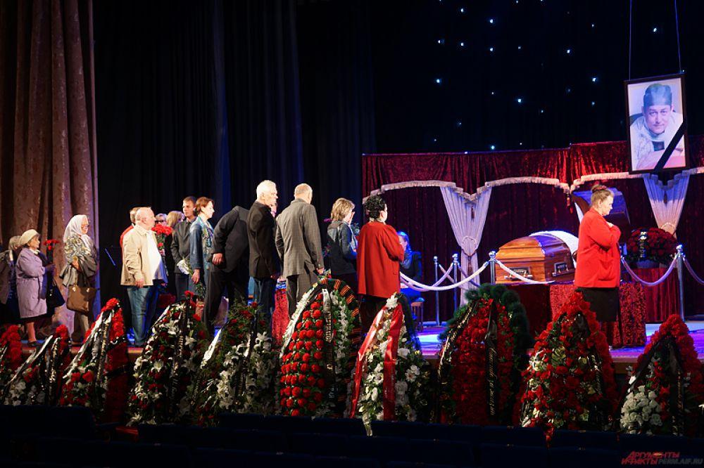 Гроб с усопшим расположили на сцене большого зала.