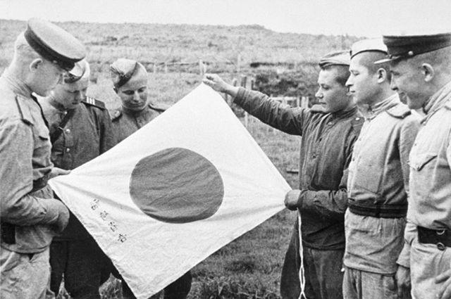 Советские воины рассматривают брошенный при отступлении японский флаг.