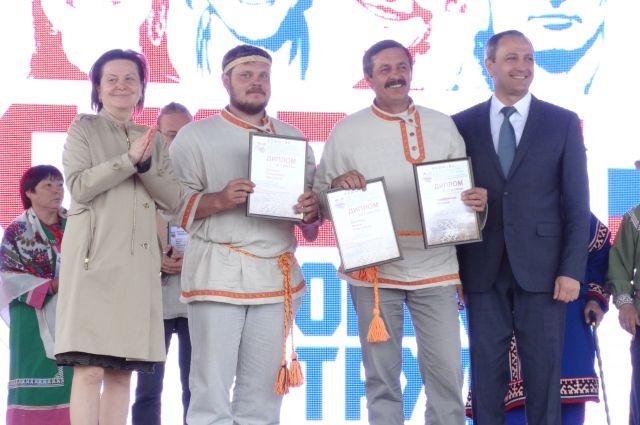 Глава Югры Наталья Комарова и главный федеральный инспектор по Югре Дмитрий Кузьменко награждают отца и сына Деняевых.