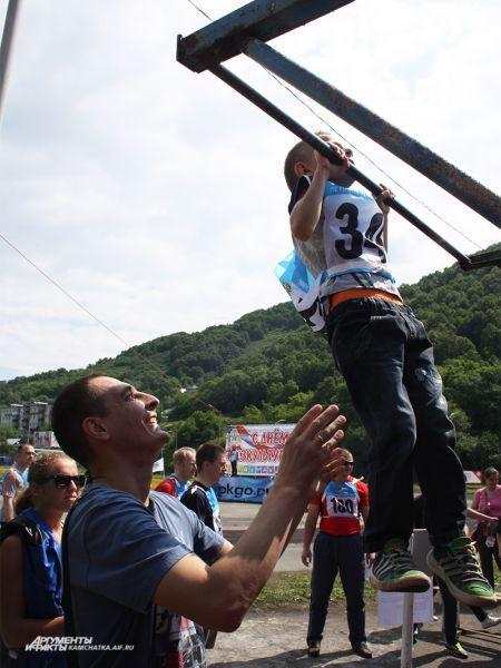 Юного участника спортивного праздника страхует папа.