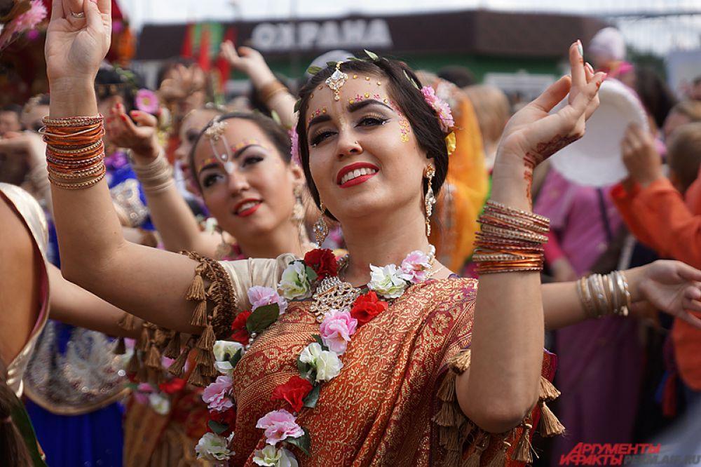 Около 500 пермяков под зажигательные танцы прошлись рядом с деревянной конструкцией, украшенной цветами.