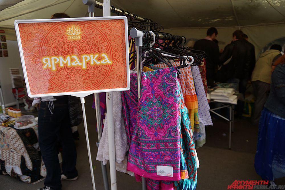 Ярмарка товаров с различными платьями и сувенирами.