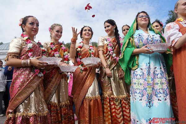 Девушки в ярких костюмах кидали в небо сотни лепестков роз.