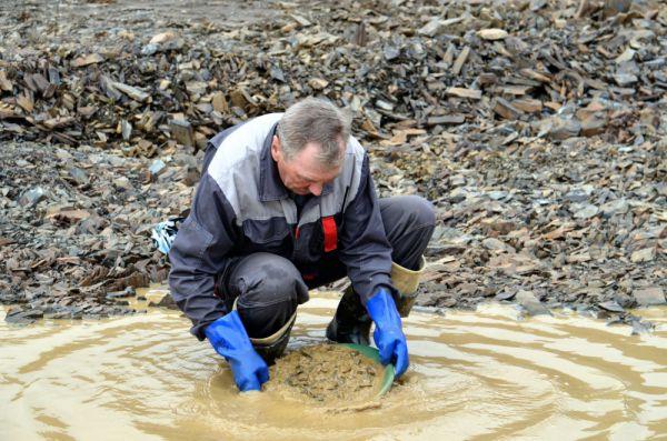 Работник прииска демонстрирует, что золото можно намыть здесь в любой луже по старинке