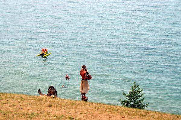 Приезжий шаман бьет в там-там, стоя на выступе скалы.