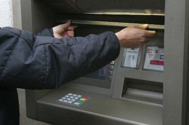 Полицейский изымает скиммер с банкомата.