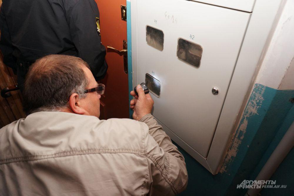 Электромонтер сверяет показания счетчиков.