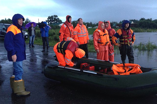 Спасатели готовятся к выходу в рейд по разлившейся реке.