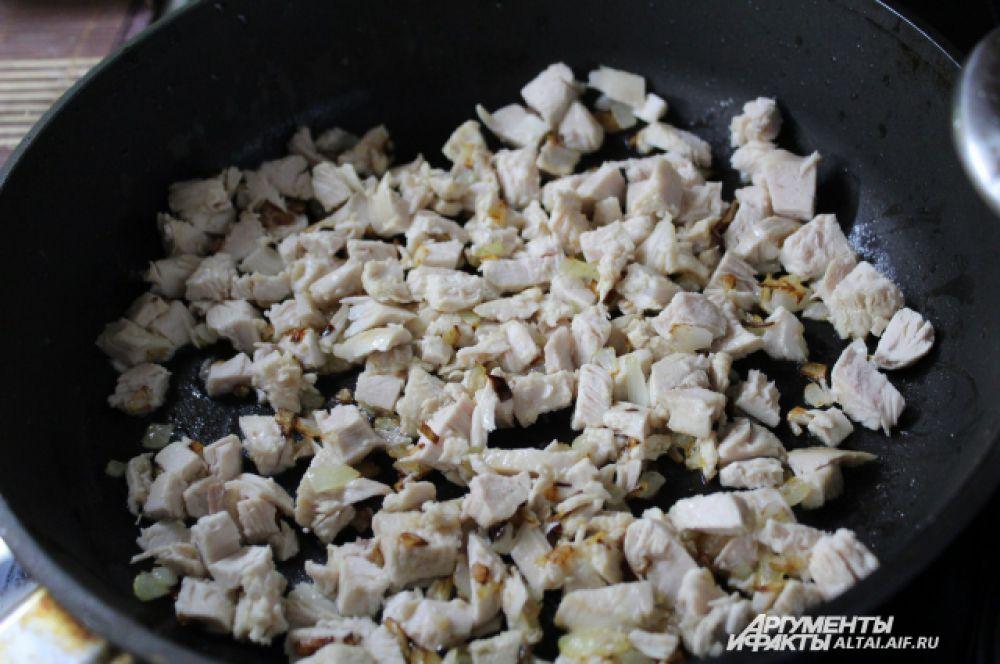 Режем куриное мясо кубиками и добавляем к луку. Жарим 5-7 минут. Солим, перчим.