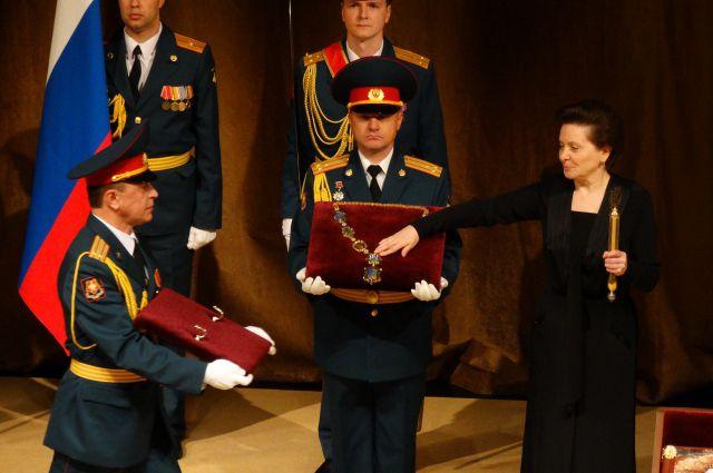 Наталье Комаровой вручают символы государственной власти.
