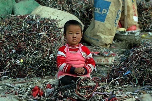 Маленький ребенок, сидящий на кабелях и электронном мусоре в Китае. Огромное количество электронного мусора регулярно (и часто нелегально) грузится на корабли, которые везут его из Европы, США и Японии в страны Азии. Гринпис призывает производителей полностью исключить токсичные материалы из своих продуктов.