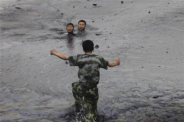В 2010 году в Китае произошел разлив нефти в портовом городе Далянь. На этом снимке рабочие, пытавшиеся отремонтировать подводный насос, попали в вязкое нефтяное пятно, один из них погиб. Фотография облетела мир как иллюстрация тех опасностей, с которыми сталкиваются люди и природа в результате работы нефтяной промышленности.