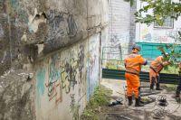 Рабочие укрепляют подпорную стену.