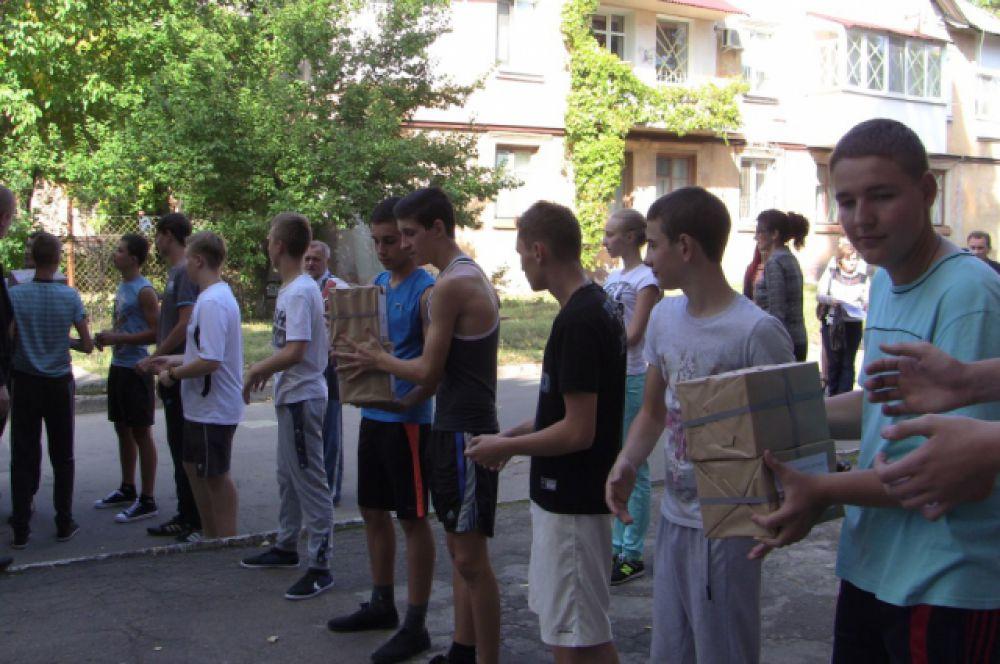 Украинские школьники разгружают книги, по которым уже завтра им придётся готовиться к выпускным экзаменам.