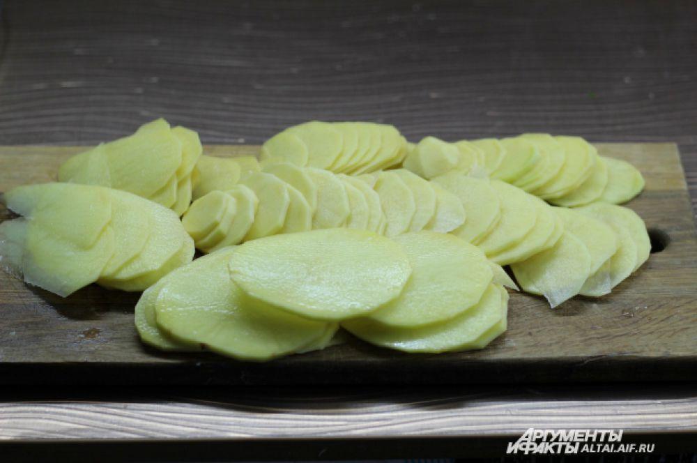 Картофель чистим, режем на тонкие кружочки и выкладываем на противень так, чтобы не было видно дна. Выкладываем по принципу мозаики.