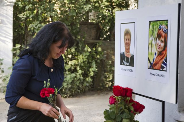 Цветы к портретам медиков, которые трагически погибли в результате нападения на вторую подстанцию скорой помощи в Симферополе.