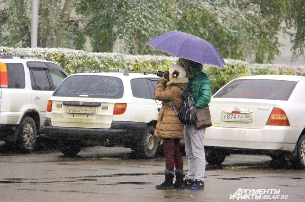 Туристы, несмотря на погоду, изучают Иркутск.