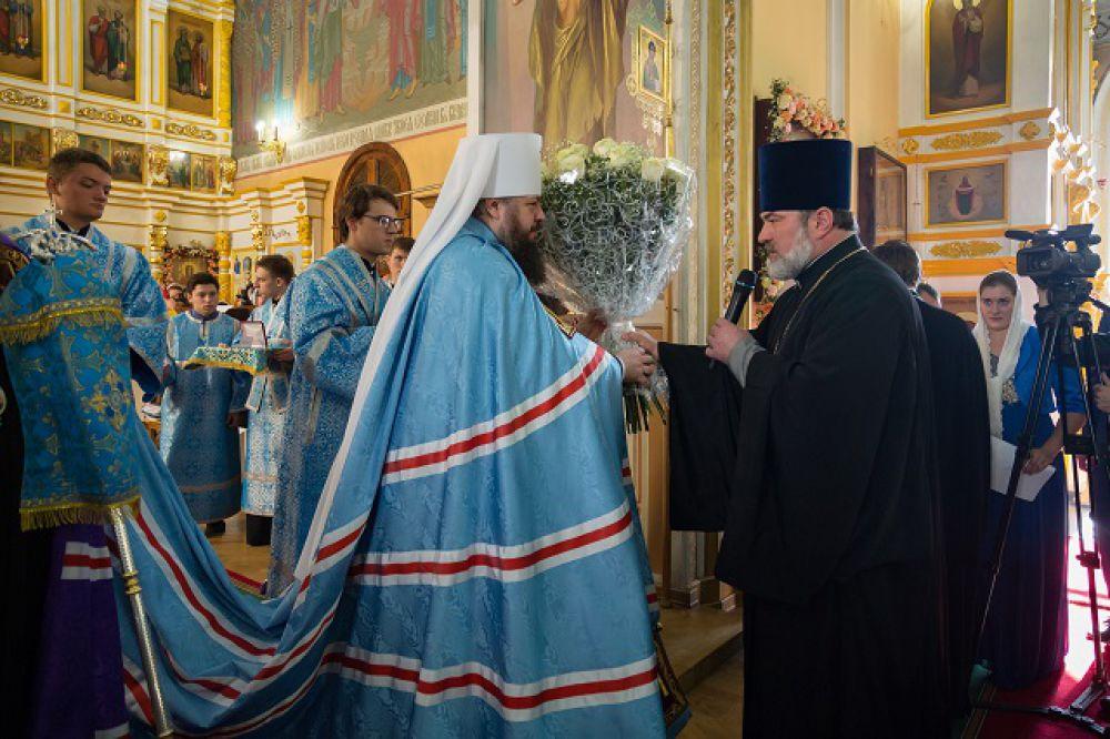 Митрополит вручает настоятелю медаль «За благие дела».