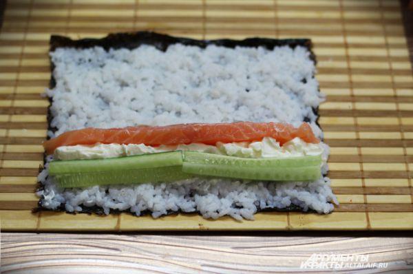 7. Когда рис выложен, начинаем выкладывать начинку. Делать это нужно быстро, для того чтобы наши нори не сильно размякли от риса. Отступаем от края 3 сантиметра и ложечкой выкладываем творожный сыр, потом выкладываем на него рыбу и огурец.
