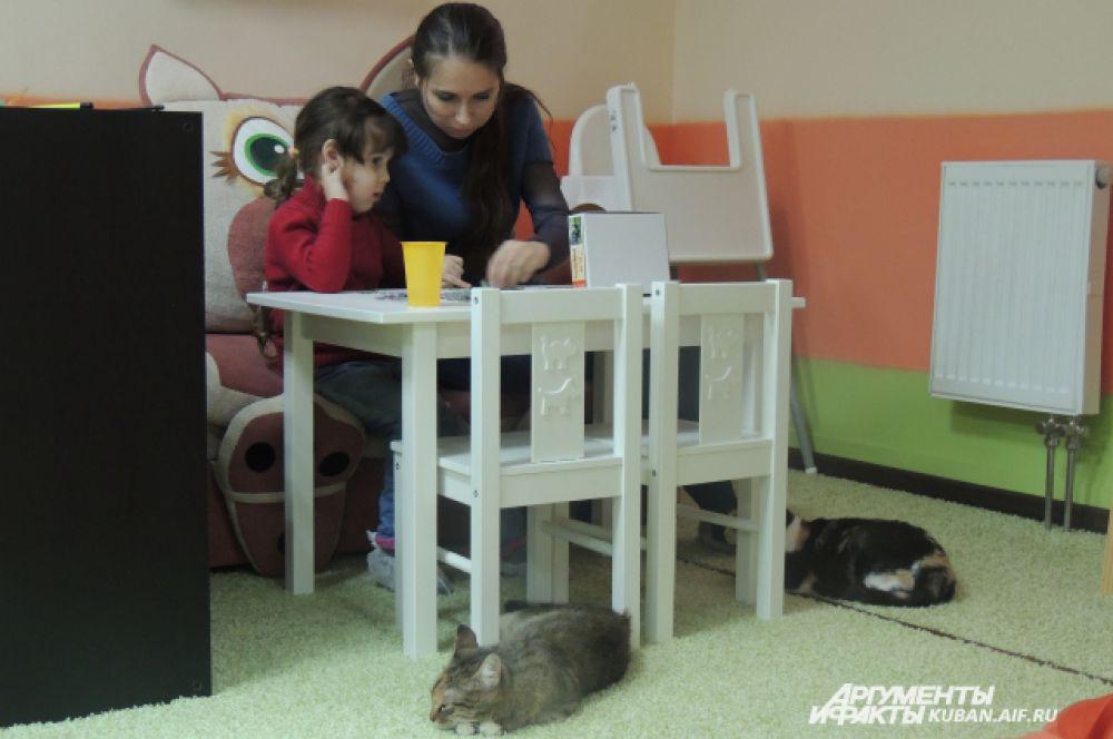 Вот так в окружении кошек маленькая Яна с мамой складывают пазл.