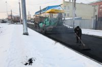 Омичи возмущены действиями дорожников, укладывающих асфальт в условиях снегопада.