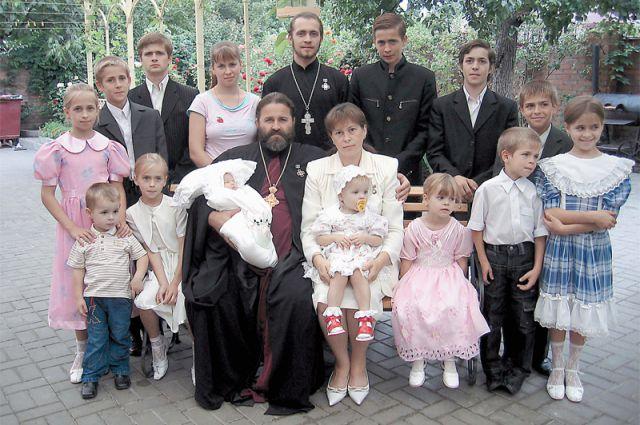 Фото сделано 6 лет назад. Несколько детей на него не попали. А две старшие девочки на фото успели выйти замуж и подарить родителям внуков. Малышка, что на руках у о. Иоанна, пошла в школу.