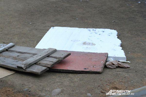 Этими досками прикрыты следы крови. Именно на этом месте лежали тела пострадавших.
