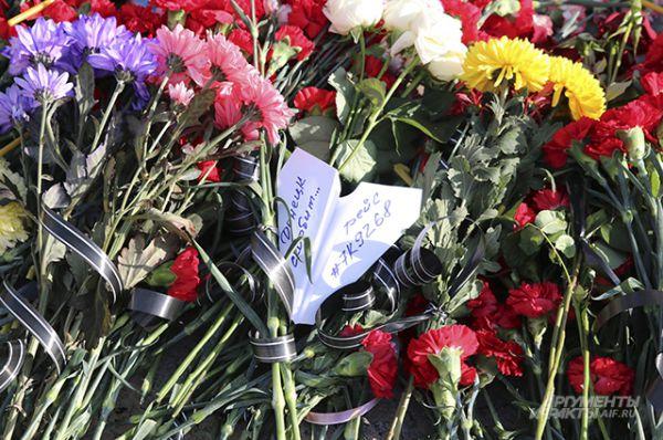 Цветы у подножия скульптуры Архангела Михаила на площади у Свято-Преображенского кафедрального собора в Донецке.