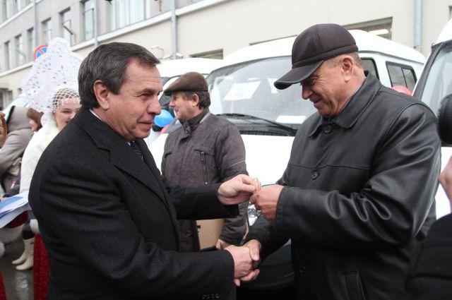 Владимир Городецкий вручает селянам ключи от автомобилей.