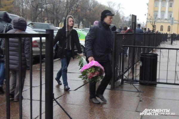Петербуржцы несли в храм цветы.