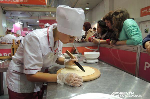 Студентка краснодарского торгово-экономического колледжа готовит пиццу под пристальным вниманием посетителей форума.