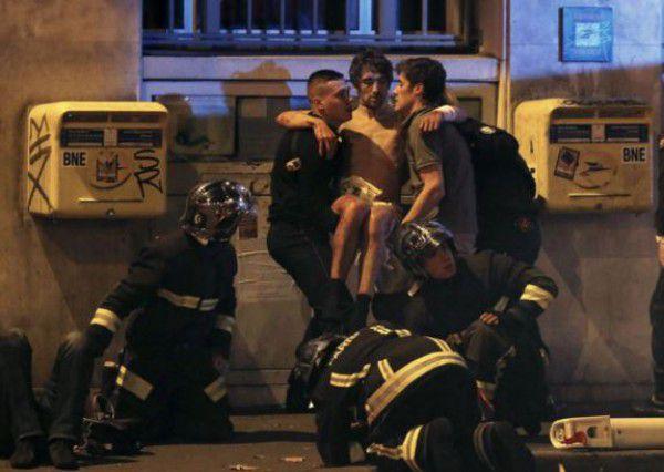 Полиция оказываэт помощь пострадавшему на концерте во время теракта