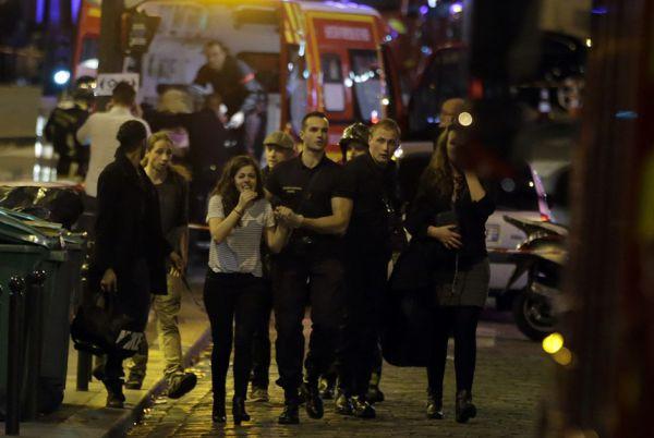 Полицейский сопровождает девушку, пострадавшую на концерте во время теракта