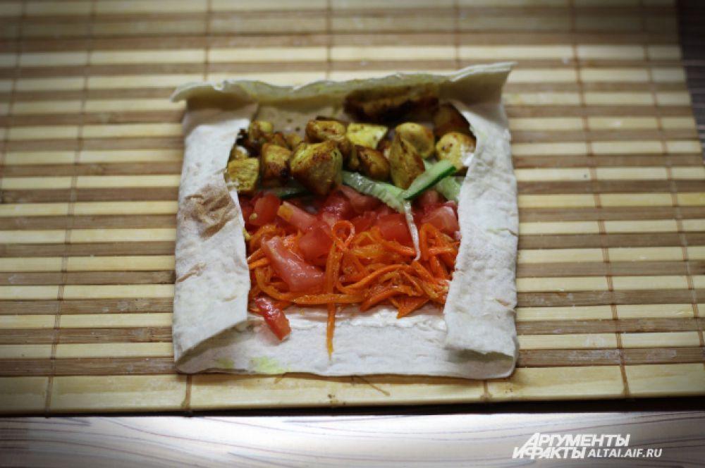 Далее рядками выкладываем овощи и мясо, совсем не много, так как шаурма у нас «мини». И заворачиваем края вовнутрь.
