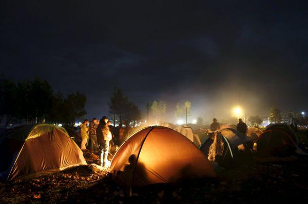 Лагерь беженцев. Люди пытаются согреться с помощью открытого огня рядом с палатками, Идомени.
