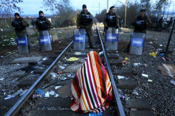 Иранский мигрант сидит на железнодорожных путях на греческо-македонской границе.