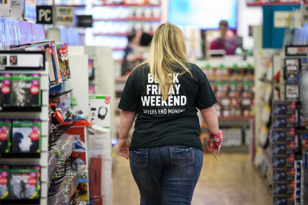 Сотрудница магазина в футболке с надписью «Черная пятница», Манчестер, Великобритания.