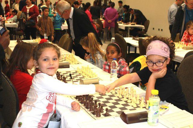 За шахматной доской дети общаются на каком-то своём языке. Эвелина (слева) с соперницей.
