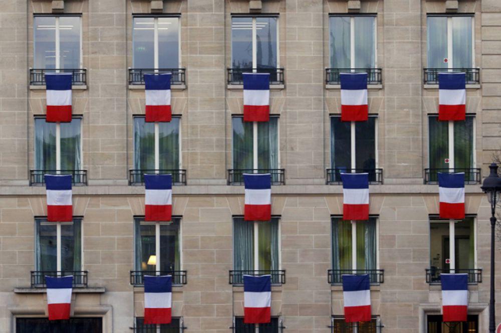 Французские флаги на жилом здании рядом с местом проведения церемонии.
