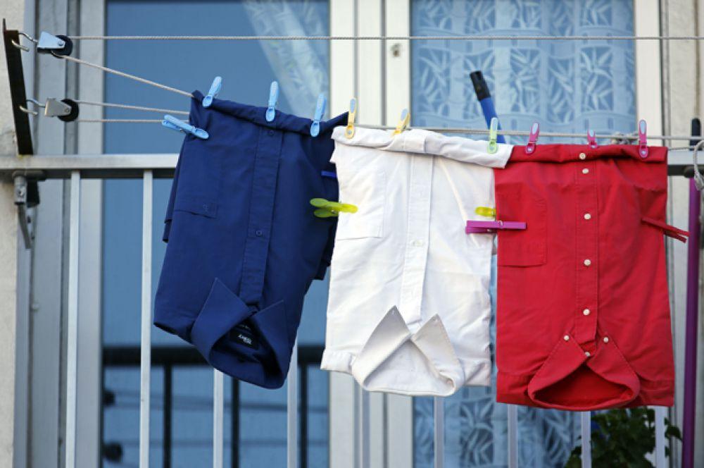 Синяя, белая и красная рубашки на балконе жилого дома.