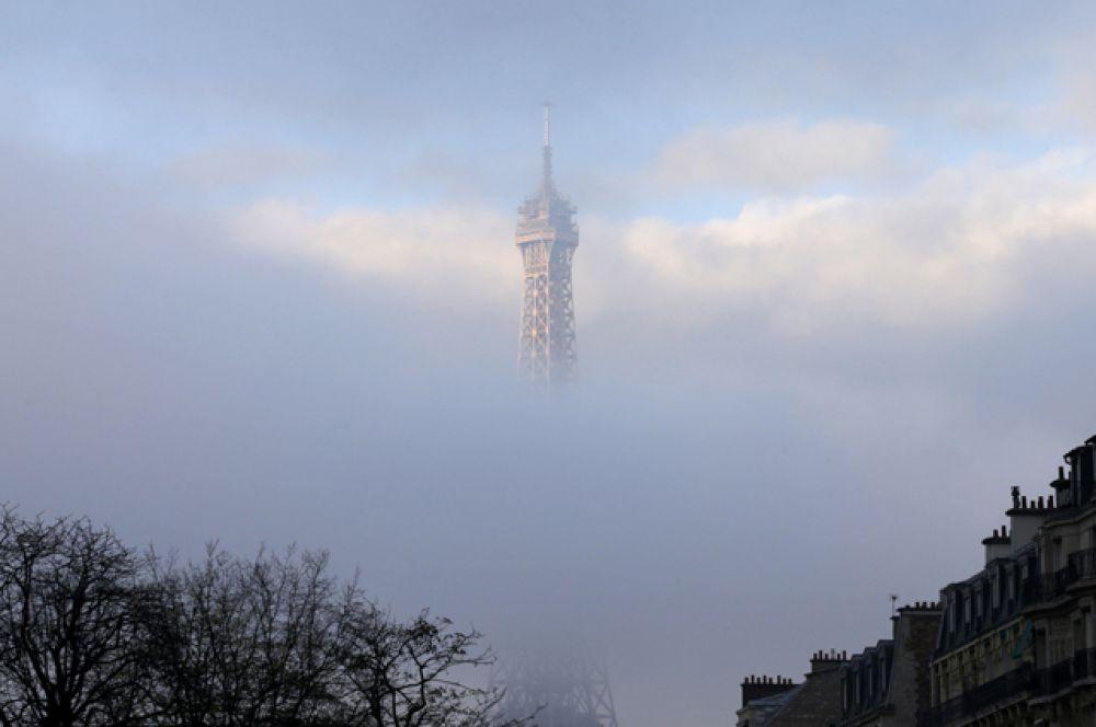 Эйфелева башня в это утро была окутана туманом.